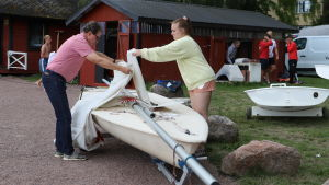 Två personer viker ner seglet på en Zoomjolle.