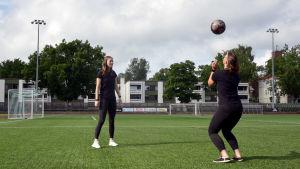 Två unga kvinnor står och sparkar en fotboll till varandra på en konstgräsplan.