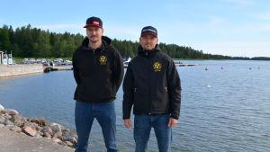 Två män står på en brygga framför vatten.
