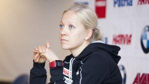 Kaisa Mäkäräinen sitter vid ett bord under en presskonferens.