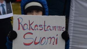 """Ett asylsökande barn visar upp en skylt med texten """"Rakastamme Suomi""""."""