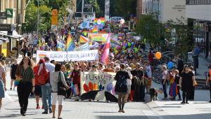 Pridemarsch med många personer vandrar genom Åbo centrum.