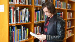 En ung man står framför en bokhylla. Han håller i en bok.