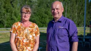 En kvinna och en man står framför kameran. Kvinnan har orange skjorta, mannen en lila.