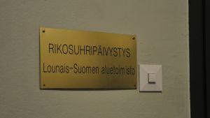 En skylt i guld med texten Rikosuhripäivystys som finns utanför brottsofferjouren i Åbo.