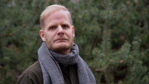 Man med skägg står ute med grå halsduk om halsen i grått väder och ser rakt in i kameran.
