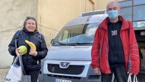 En kvinna och en man står bredvid varandra, framför en bil och ett hus. De har kassar i händerna, kvinnan håller också i en banan och ett kålhuvud.