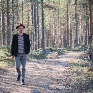 Mies hattu päässä, pikkutakki päällä ja farkut jalassa metsäisellä polulla, taustalla kellertävä koira