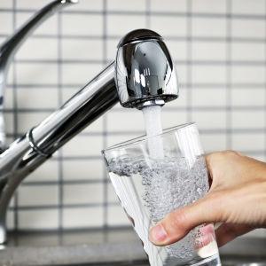 Människa fyller vattenglas under kranen