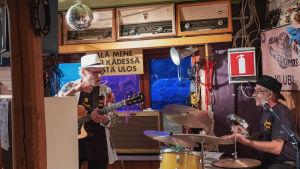 Aslak Christiansson ja Arto Tyrni soittamassa, juttelevat toisilleen baarin soittonurkkauksessa Aslak and the Eskimos -klubilla