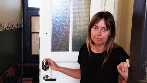 Mia Haglund har öppnat sin lägenhetsdörr och står och håller i den samtidigt som hon tittar in i kameran.