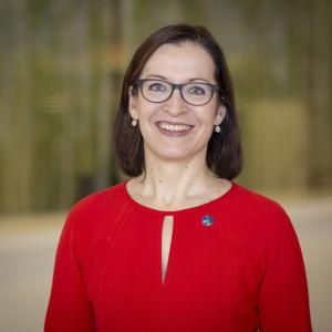 Advokatförbundets viceordförande Hanna Räihä-Mäntyharju, en dam med brunt axellångt hår, glasögon och röd skjorta.