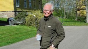 En man med vitt hår, glasögon och mörkgrön fleecejacka står med kaffemugg i handen och ler mot kameran. I bakgrunden ett stort gult trähus och ett gult högt klocktorn. Slutet på maj, soligt och grönt.