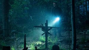 Pappa Creed lyser med ficklampa på de många korsen på djurkyrkogården.