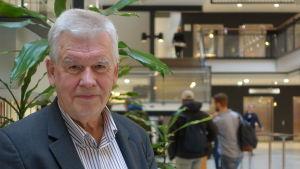 Kjell Asplund, en äldre man med grått hår i randig skjorta och kavaj står innuti en byggnad. I bakgrunden går människor och det syns en trappa till andra våningen.