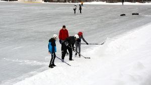Fyra pojkar söker med ishockeyklubborna efter en puck som skjutits in i en stor snöhög på en skridskobana.