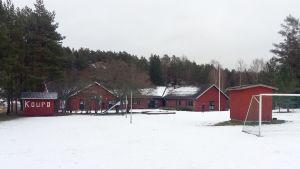 Röda låga lägerskolbyggnader.
