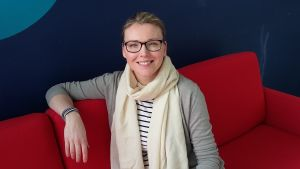 Katarina Paasi sitter på röd soffa.