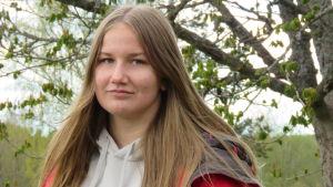 En 15-årig flicka med långt ljusbrunt hår. Hon har en röd, vintät jacka på sig och en grå munkjacka under. Hon ser in i kameran, ser allvarlig ut. I bakgrunden ett träd (lönn) som håller på att få löv. Lövsprickning.