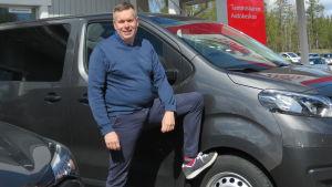 En man med kortklippt hår och blå tröja står utanför en bilaffär. Han står vid en bil med ena benet lyft och foten lutar på bilens framdäck.