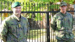 Två officerare i militäruniform står vid Nylands brigads gamla järnport.