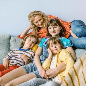Karaktären Ella med sina tre barn i en soffa.
