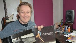 Mats Prost visar upp två LP-skivor med Bruce Springsteen och U2.