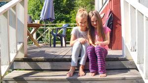 Elisha och Amina Bergroth sitter på trappan