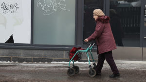 Äldre dam går utomhus med rollator.