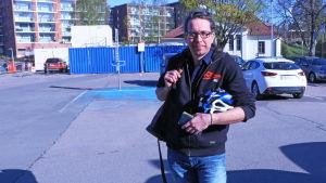 Jan Hellgren håller i en cykelhjälm på en parkeringsplats.