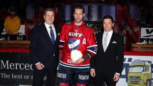 Ordförande Heikki Hiltunen (till vänster) och vd Riku Kallioniemi (till höger) från FM-ligans håll premierade HIFK:s Markus Kankaanperä för att ha spelat tusen ligamatcher.