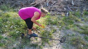 En äldre kvinna med anilinröd t-skjorta gräver med liten spade i marken. Bredvid sig har hon en metalldetektor. Sommar och sol.