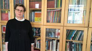 Kvinna står framför bokhylla.