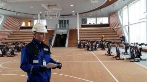 Inredningsarkitekt Patrick Terranova står med vit skyddshjälm i idrottshallen med spinningcyklar och basketkorg ombord på kryssningsfartyget Mein Schiff 1, byggt på Åbovarvet Meyer Turku.
