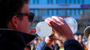 En studerande dricker direkt från en flaska.