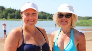 En yngre och äldre kvinna som båda har ljust hår och vit hatt och baddräkt står på en simstrand.
