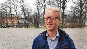 Henrik Saxén, en man med ljusr hår, glasögon och blå rock står en kylig vårdag vid ett torg med nubbstenar. I bakgrunden syns kala träd och en bro.