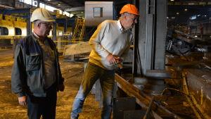 Kenneth Nordell och Göran Eriksson står intill en arbetsgrop i valsverkshallen i Dalsbruk. De har båda hjälmar på huvudet.