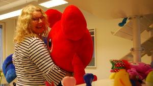Anneli Tisell med en stor röd Babblare-figur i famnen.