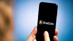 Älypuhelin, jossa näkyy OneCoin-logo.