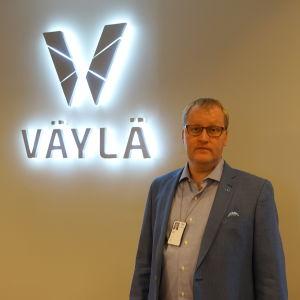 Foto på Magnus Nygård med Trafikledsverketes logo upplyst i bakgrunden.