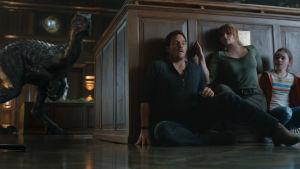 Tre rädda människor gömmer sig bakom ett bord med en dinosaurie lurande runt hörnet.