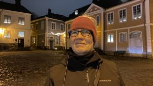 Barbro står på rådhustorget i Borgå med julljus i bakgrunden.