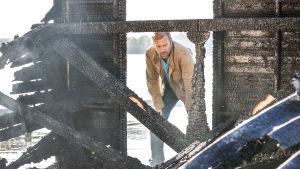 Karaktären Thomas vid en nerbränd byggnad.
