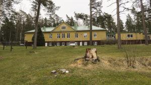 Ett gult hus med stor grön gräsmatta framför.