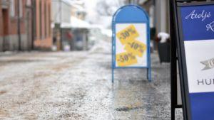 Två skyltar på isig och sandad gata. I bakgrunden tegelröda hus.