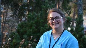 Kvinna i sjukskötarkläder står utomhus och tittar mot kameran. Bakom henne träd och buskar.