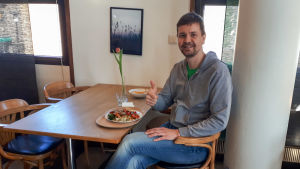 En man sitter vid ett bord och visar tummen upp.