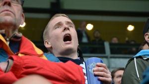 En man ropar med stor mun och hejar på sitt lag, Inter Turku under en fotbollsmatch. I handen har han en blå mugg med lagets logo.