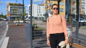 En kvinna i ljus tröja och solglasögon står vid en busshållplats i Nickby.